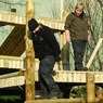 Animal keepers on giant panda climbing frames putting out enrichment for them